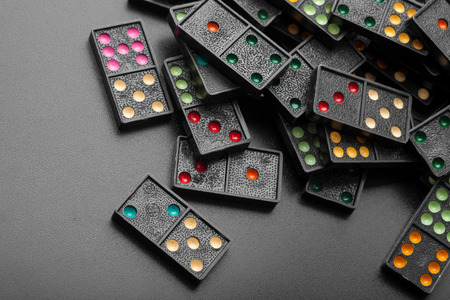 piles of black color dominoes with colorful dot game pieces lying on dark background