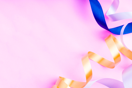 Mix colorful ribbon on a pink background with copy space