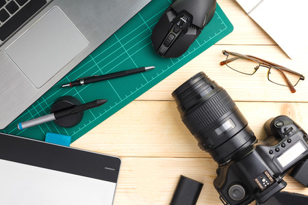 Top view of office stuff and gadgets on wooden desk with graphic designer equipment. flat lay style.