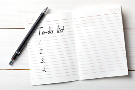 Opened personal organizer with a to do list. on white wooden background