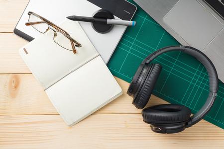 Hoogste mening van materiaal en gadgets op houten bureau met grafisch ontwerpermateriaal. vlakke lay-stijl. Stockfoto