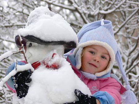 A girl embracing a snowman photo