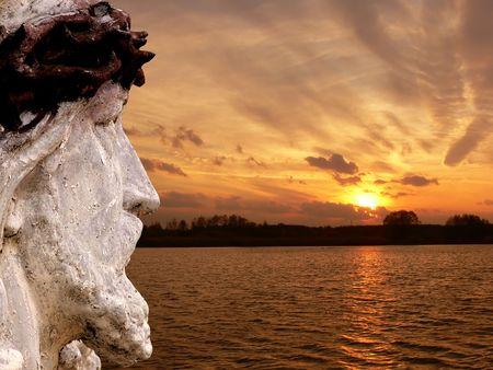 A statue of jesus against sunset landscape photo