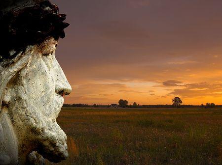 divinity: Statue of Jesus against sunset landscape Stock Photo