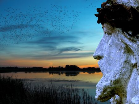 Statue of Jesus against sunset sky photo
