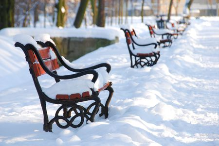 snowlandscape: Red benches in the park covered with snow Stock Photo