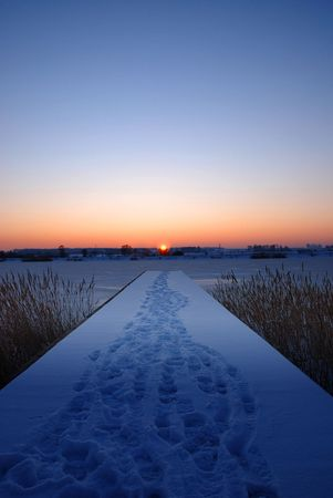 snowlandscape: A pier by a frozen lake at sunset Stock Photo