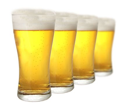 Four glasses of beer against white background photo