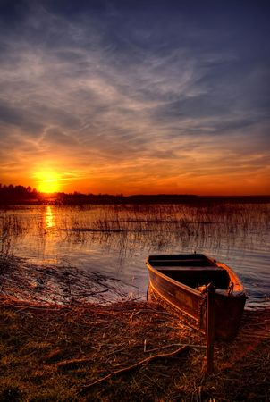 fishing lake: A boat by the lake at sunset Stock Photo