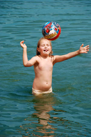 A girl playing with a ball in water photo