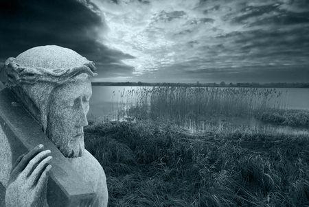 Stone statue of Jesus bearing the cross photo
