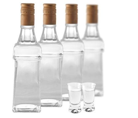 Botlles of vodka and shotglasses on white background photo