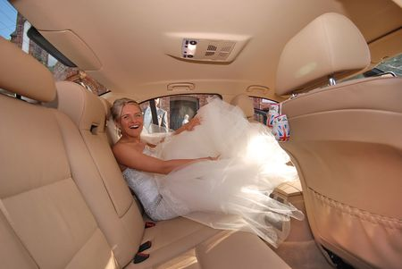 Bride getting in to a limousine photo