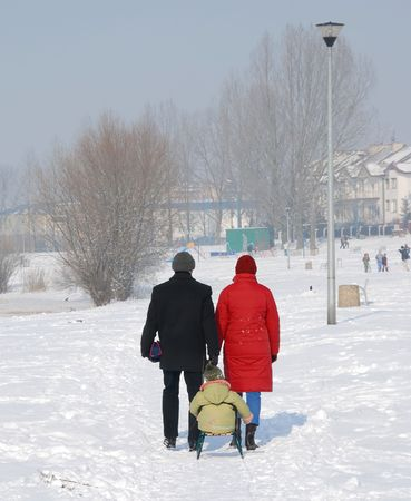 A couple with a child on sled walking in the snow photo