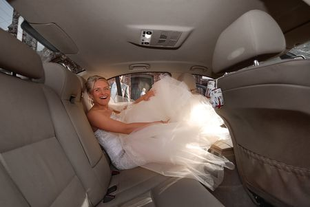 Beautiful young bride getting into a limousine photo