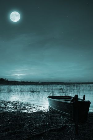 Moon and stars over a boat by a lake photo