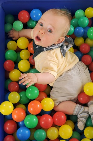 playcentre: Cute boy playing in a pool of plastic balls Stock Photo