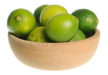 Wooden bowl filled with limes isolated on white background photo