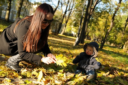 toddler playing with mummy in the park in autumn photo