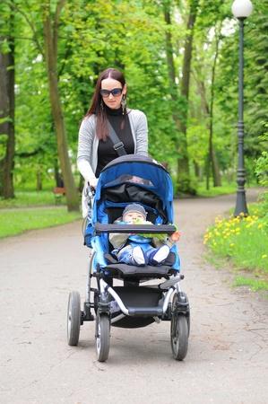 poussette: Jeune femme avec une poussette, marcher dans le parc