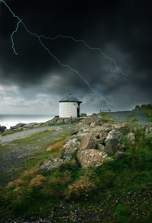 Lightning strike and strong wind blowing by the ocean in Land photo