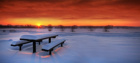 spectacular: Spectacular winter sunset with a table and benches covered with snow