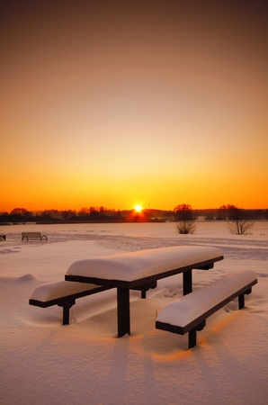 Beautiful winter sunset with a table and benches photo