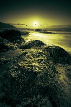 mare agitato: Bella spiaggia rocciosa dal mare immersa nella luce dorata Archivio Fotografico