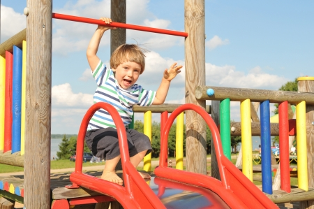 Cute happy little boy playing in the playground in summer Banco de Imagens