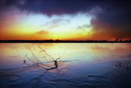 Frozen lake and dark clouds at sunset  photo