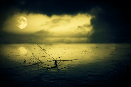 Frozen lake in moonlight with stormy clouds Stock Photo