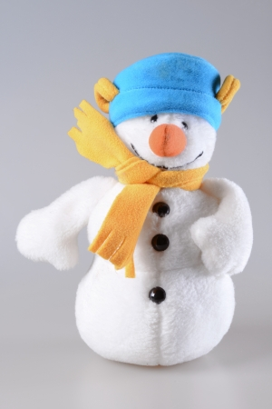 White toy plush snowman on grey background photo