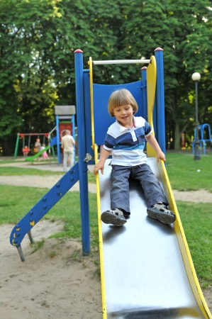 Little boy going down a slide photo