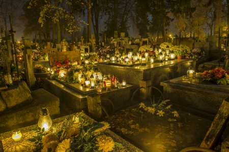 all saints  day: Cemetery in Poland on All Saints Day illuminated with candles Stock Photo