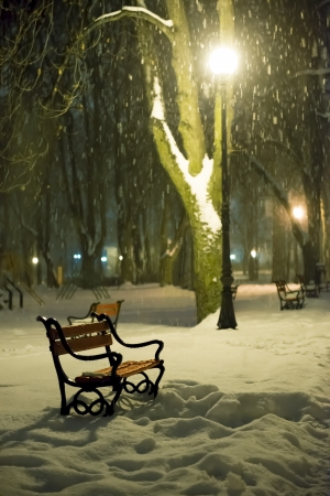 night scenery: Red bench in the park with falling snow at night Stock Photo