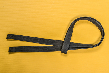 Martial art black belt isolated on yellow mat background Stock Photo