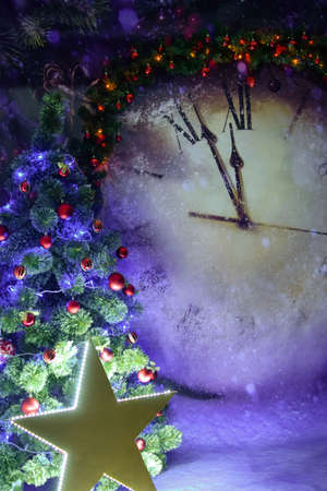 Christmas tree illuminated by a large luminous star on the background of a huge Christmas clock Foto de archivo
