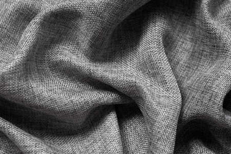 Gray fabric texture with folds. Cotton fabric background.