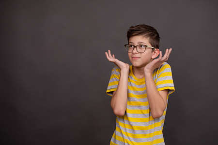 Boy spread his hands to the sides, as if he did not take a anything. Studio shot on a gray background. Teenager with glasses.