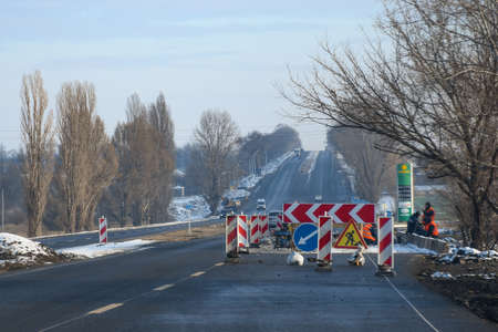 Road works, horizontal. Gas station on the right side.