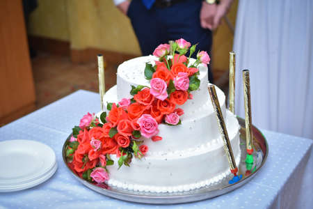 A large beautiful wedding cake is decorated with rose flowers.