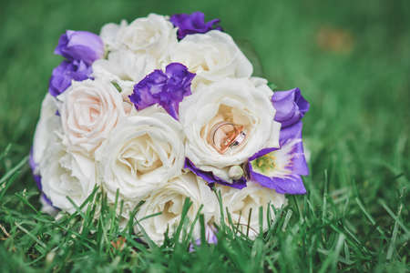 A small bouquet with two wedding rings on the green grass.