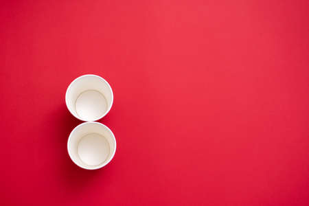 Two empty paper cups in the shape of the number 8. On a red background. Copy space for text