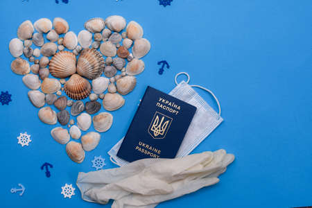 Heart-shaped shells on a blue background. Travel and recreation during quarantine. Medical mask, biometric passport of Ukraine, medical gloves. layout, mock up