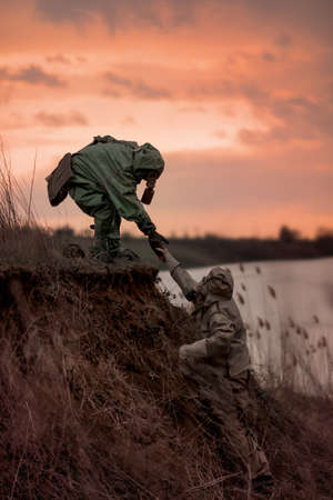 People in gas masks and radiation protection suits run away from radiation contamination. Stockfoto