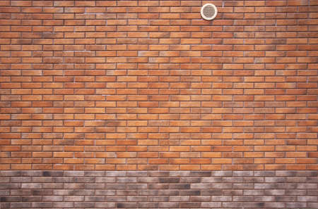The wall is made of red brick with brown edging.