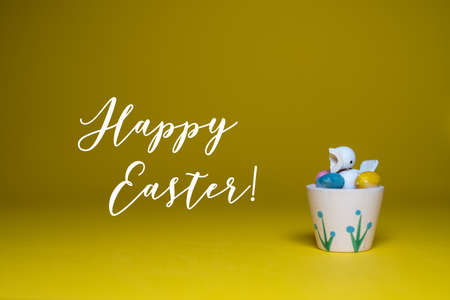 Happy Easter greeting card background with text. Cute little chick with colorful Easter eggs on yellow background.