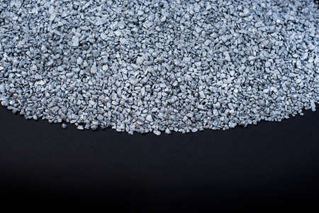 Pile of small silver particles on dark gray background