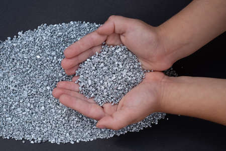 Small hands holding silver particles on dark gray background