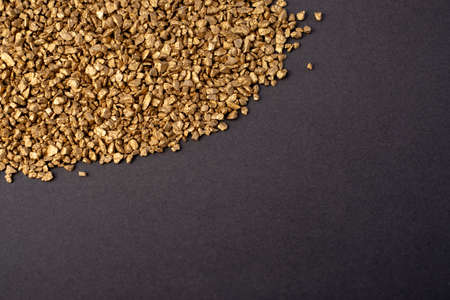 Pile of small gold particles on dark gray background